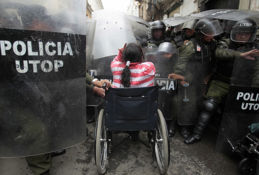 A physically disabled woman on her wheelchair clashes with riot police in the centre of La Paz