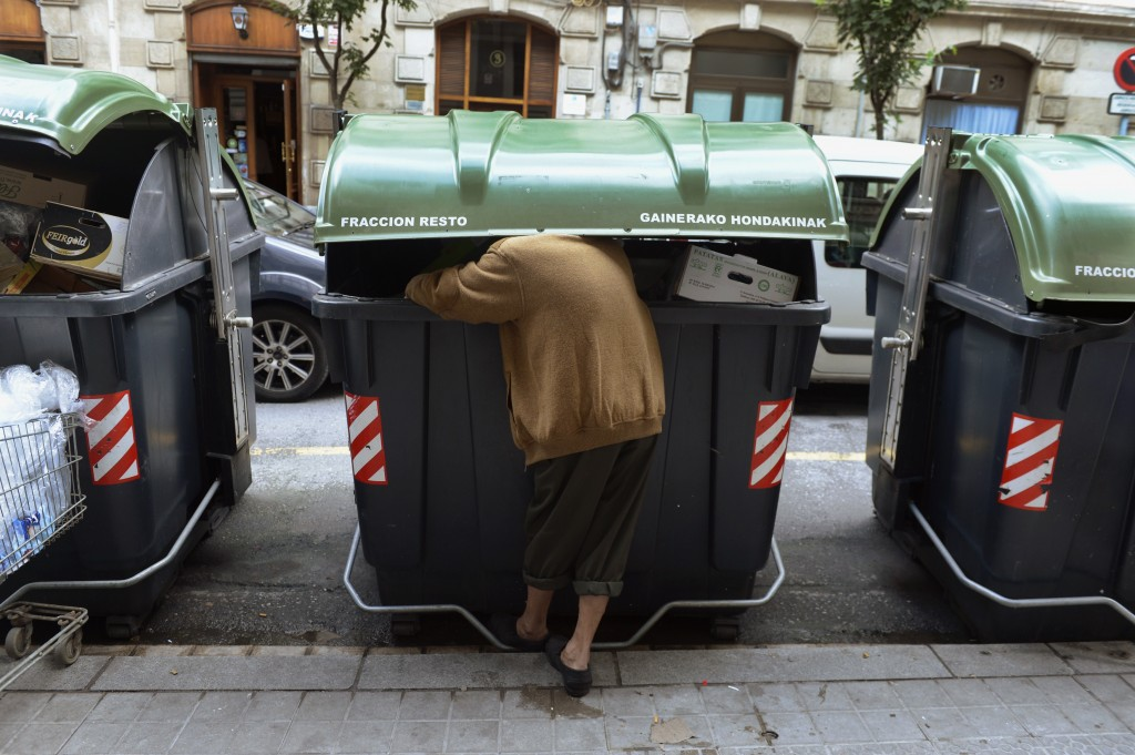 Man searches for food in container outside a supermarket in central Bilbao
